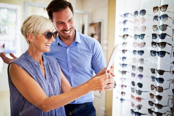 Pretty mature woman is choosing new glasses at optics store