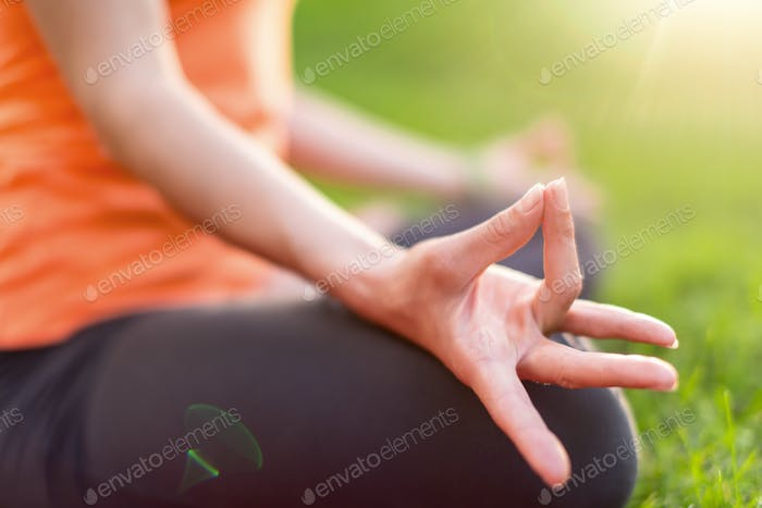 girl meditating and doing yoga at sunset