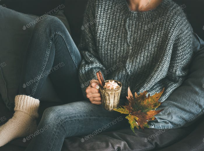 Woman in woolen sweater holding mug with hot chocolate