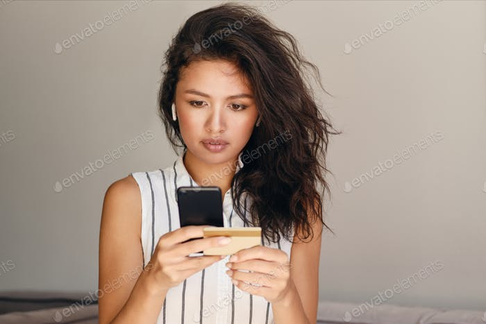 Young attractive Asian woman in wireless earphones with credit card thoughtfully using cellphone