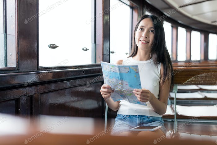 Woman checking location on paper map in ferry