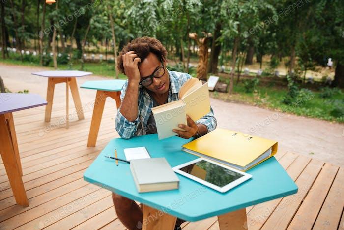 Pensativo africano Hombre la lectura y el estudio