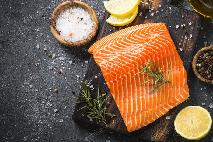 Salmon fillet with ingredients for cooking on black