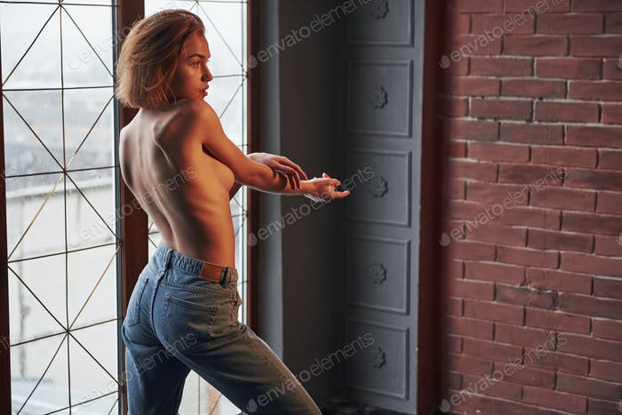 Touching the hand. Hot young blonde with bare chest and jeans stands against the window