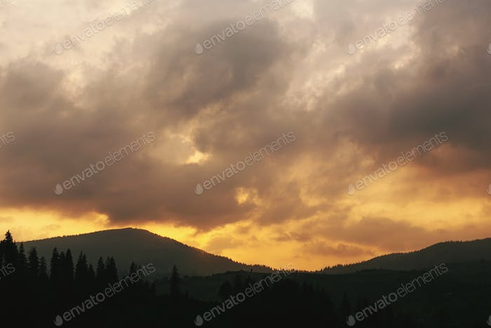 Amazing sunset in mountains landscape, sun and clouds and woods in sunlight