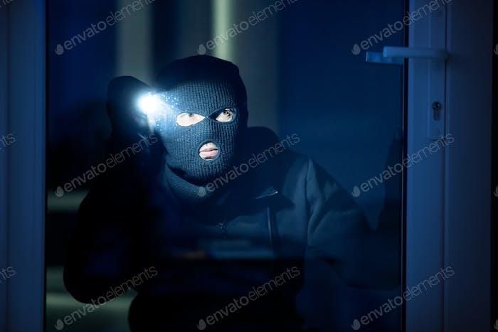 Eindringling bricht in Wohnung oder Büro mit Blitzlicht