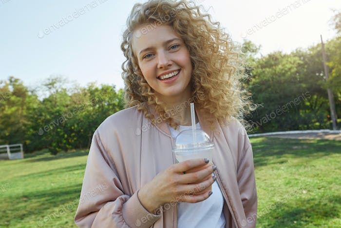 Close up of attractive young beautiful girl blonde with curly hair walks in the park