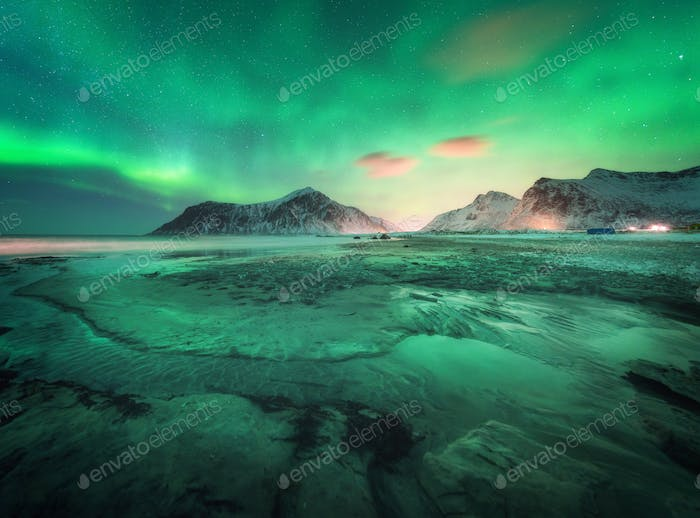 Aurora borealis above the snowy mountains and sandy beach