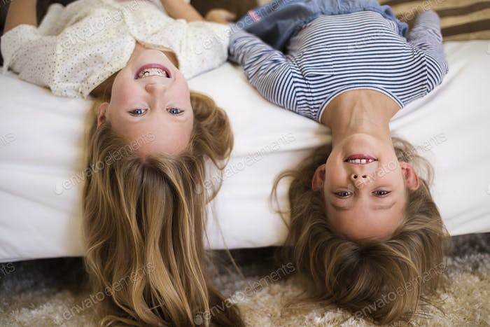 Cheerful girls upside down on the couch