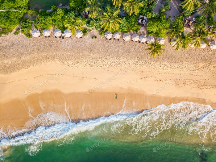 The guy lies on a sandy beach on a tropical island. Drone view