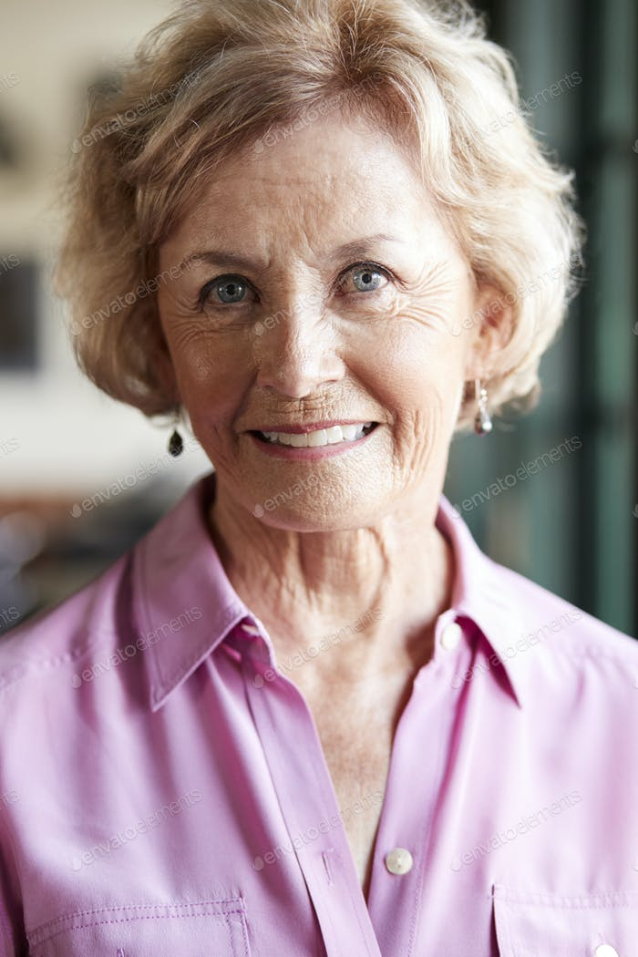 Portrait Of Smiling Senior Woman Sitting In Restaurant