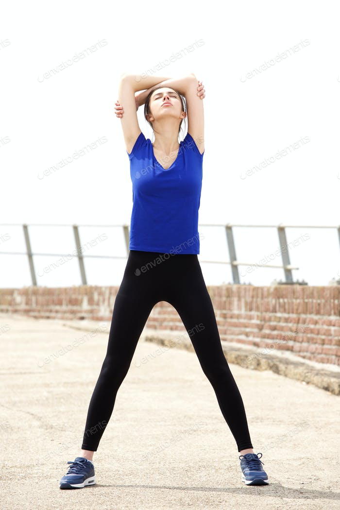 Sporty young woman stretching arms above head