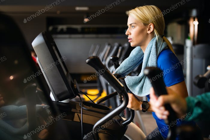 Attractive fit young woman using a step machine in the gym
