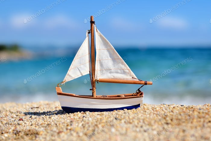 Miniature toy sailboat on the beach against the background of th