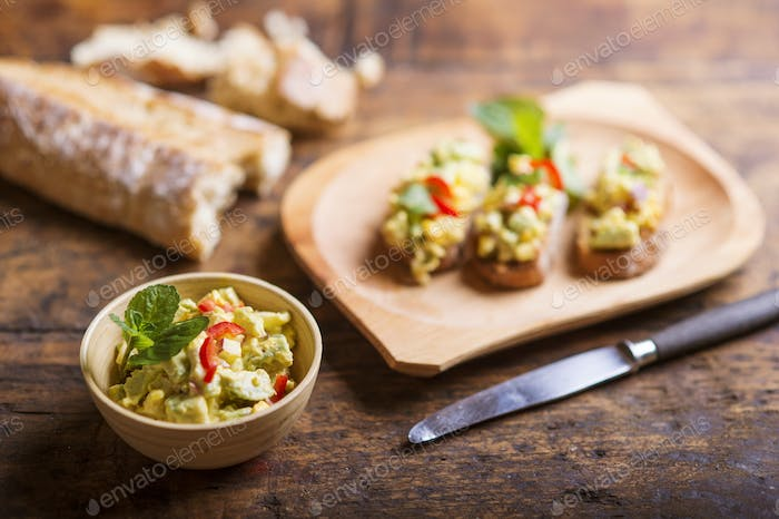 Avocado spread on slices of bruschetta against wooden table