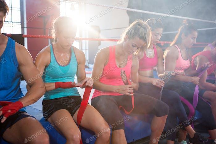 Zurück beleuchtete Athleten sitzen auf Boxring während Wickeln Bandagen