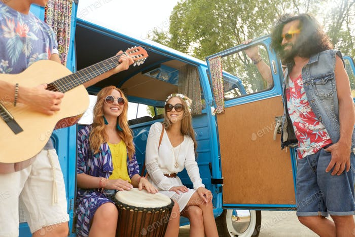 happy hippie friends playing music in minivan
