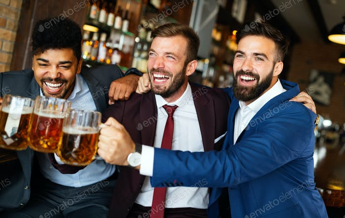 Men fans screaming and watching football on TV and drink beer in a pub