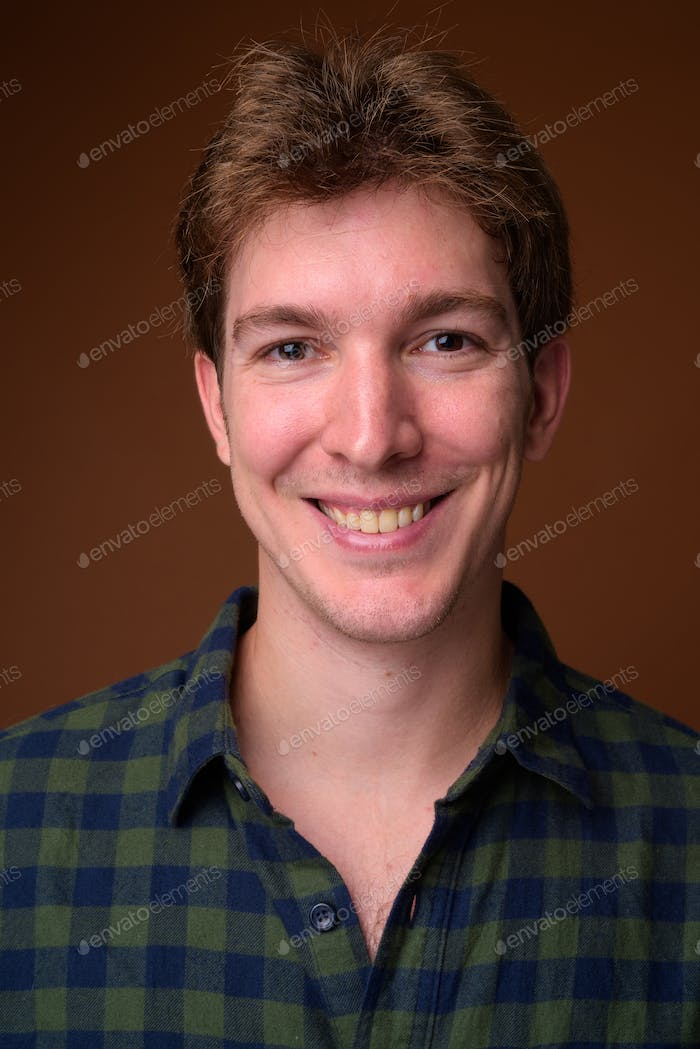 Face of young handsome hipster man in green checkered shirt