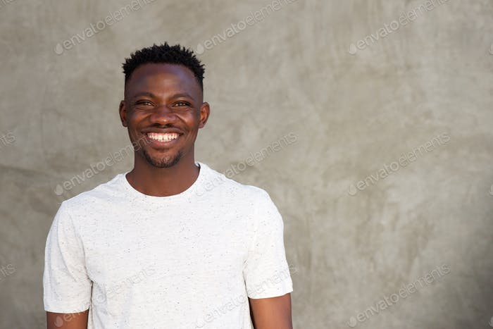 cheerful african man smiling by wall with copy space