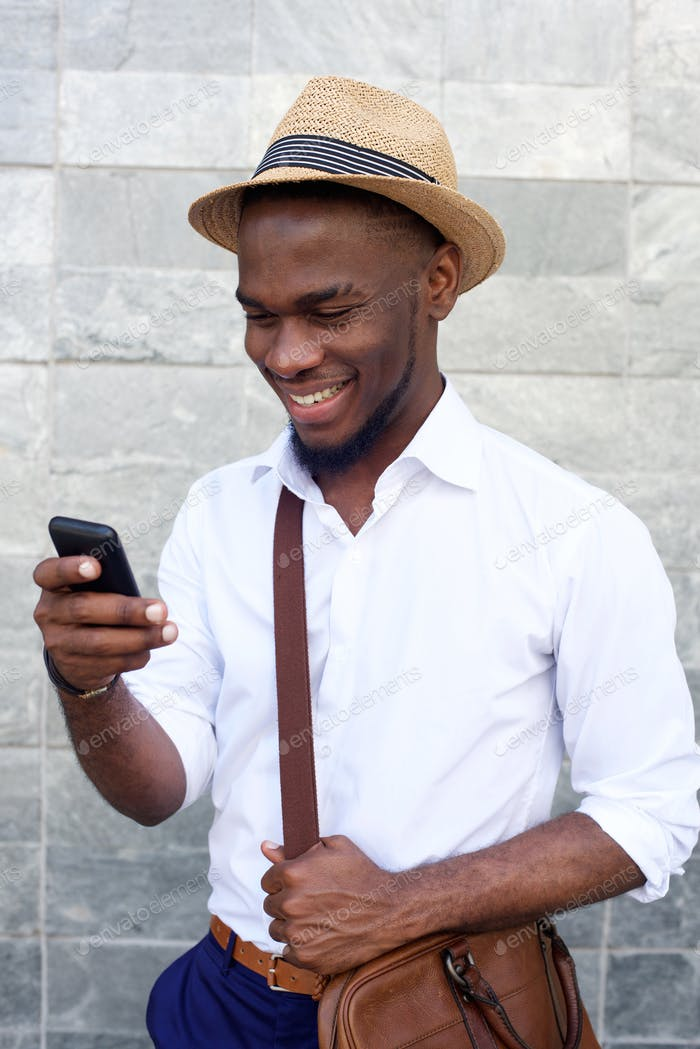 Handsome young guy reading text message on mobile phone