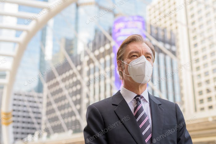 Mature businessman with mask for protection from corona virus outbreak thinking at skywalk bridge