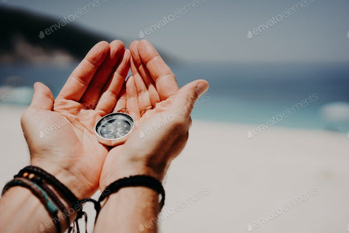 Man's hand holding compass against the backdrop of beach and sea. The concept of travel, summer