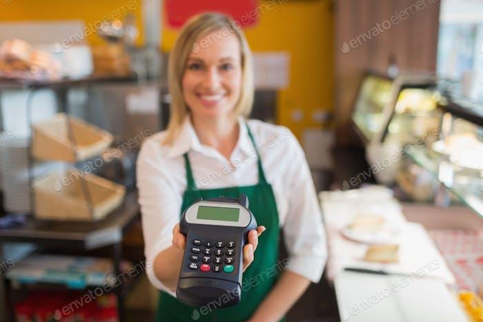 Portrait of female shop owner holding credit card reader in bakery