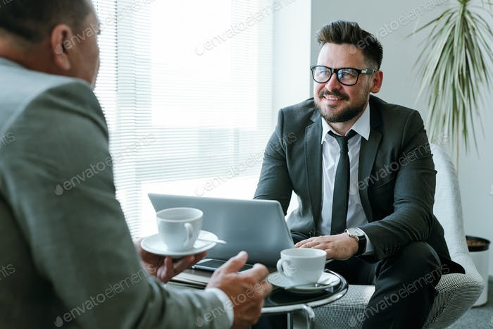 Happy young businessman in suit and eyeglasses looking at his business partner