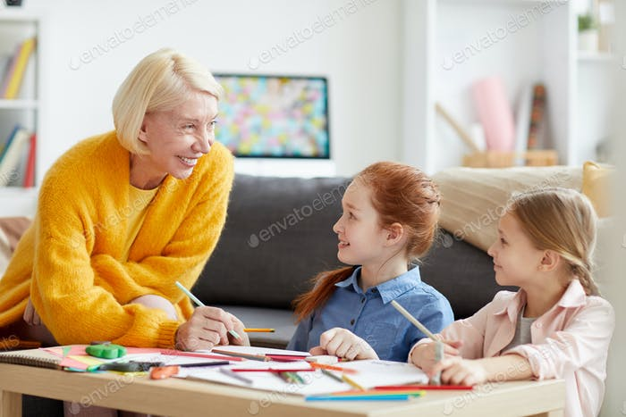 Smiling Mature Woman Drawing with two Kids