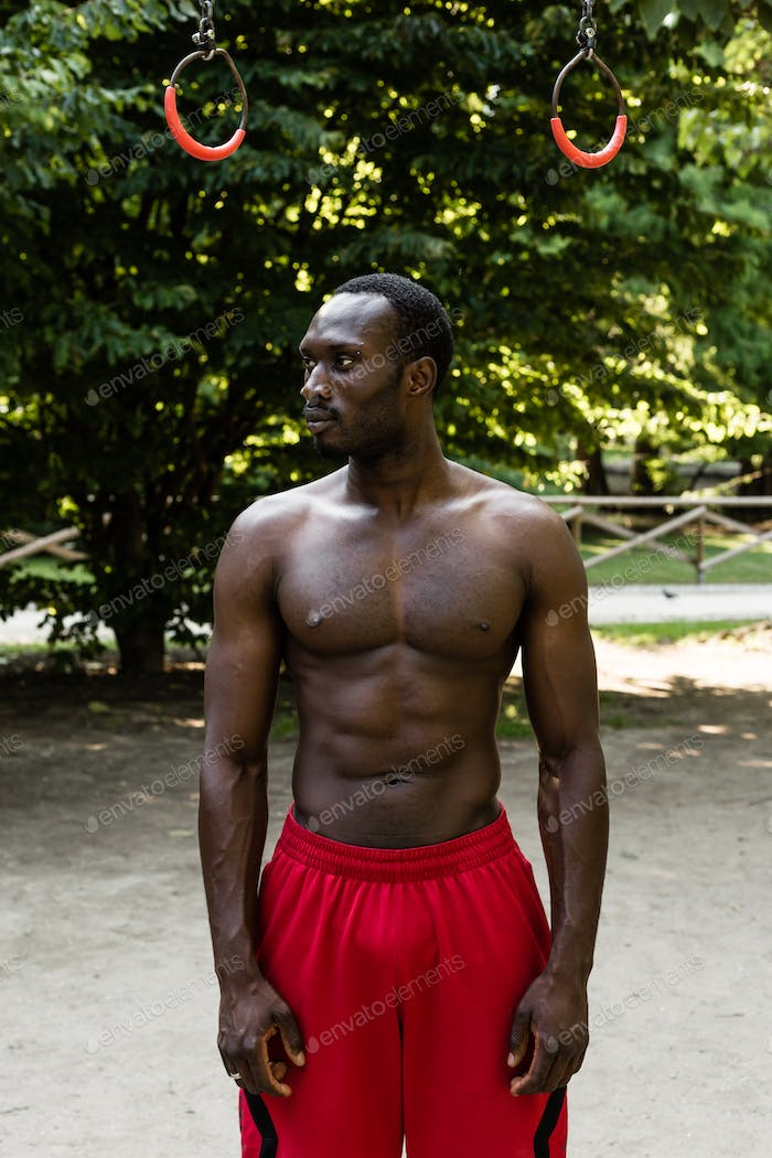 Athletic black man posing in a city park