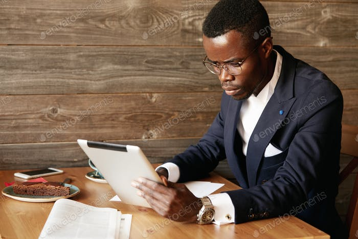 Serious young African American businessman holding digital tablet, looking at the screen with concen