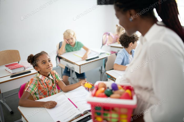 Little girl taking colored ball from teacher at the lesson