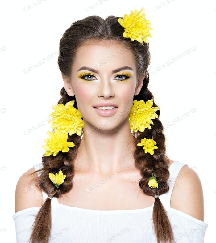 Gesicht einer jungen lächelnden Frau mit leuchtend gelben Make-up.