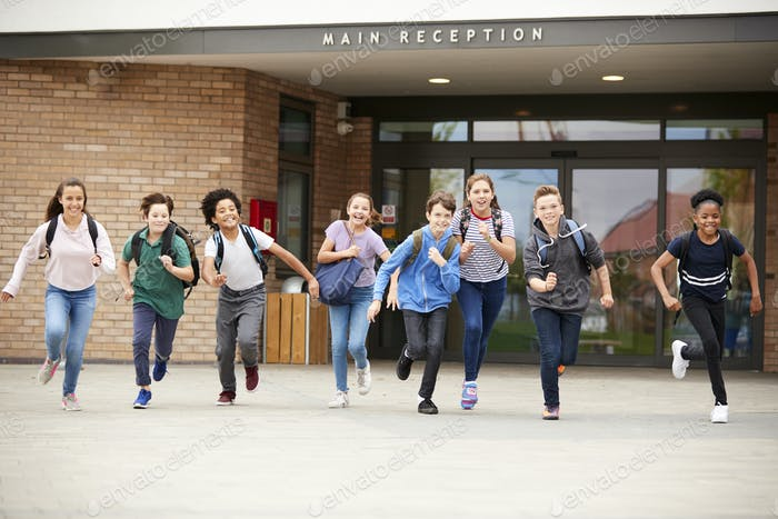 Group Of High School Students Running Out Of School Buildings Towards Camera At The End Of Class