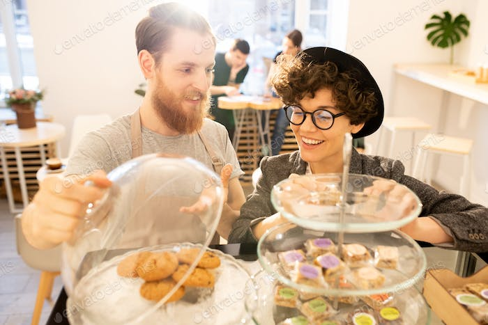Waiter presenting sweets to customer in cafe