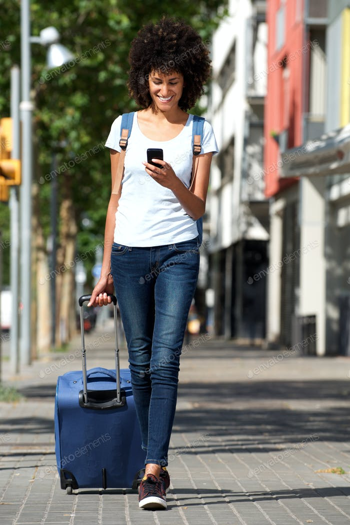 Full length happy traveler walking on street with suitcase and smart phone