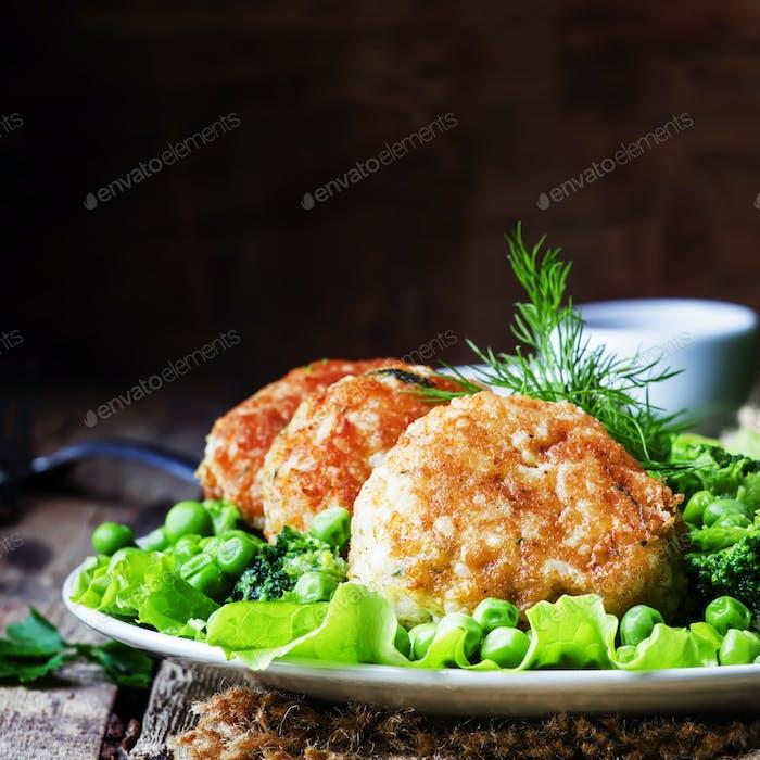 Fischkoteletts oder Fleischbällchen von Kabeljau und Zander mit einer Beilage von grünen Erbsen