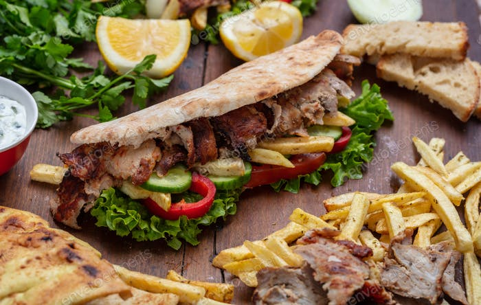 Gyros, Shawarma, zum Mitnehmen, Straßenessen. Sandwich mit Fleisch auf Holztisch