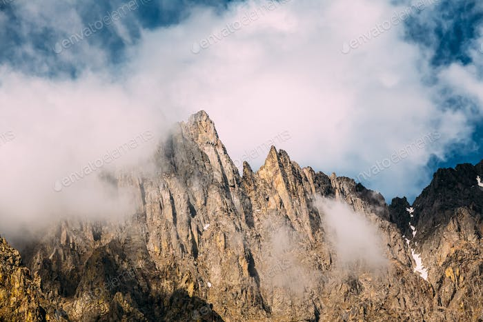Clouds fly low over the rocks. The varied mountain landscape in