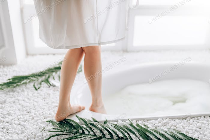 Woman in white bathrobe dips legs into the bath
