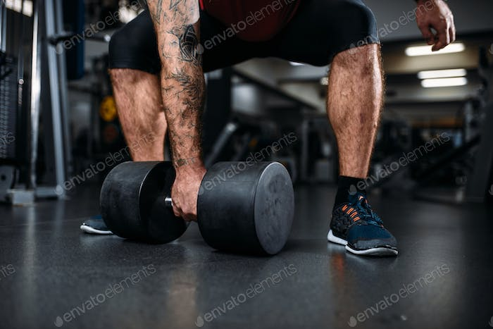 Male person with dumbbell, training in gym