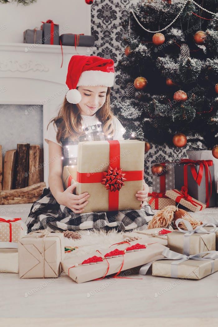 Beautiful girl in santa hat unwrapping christmas presents
