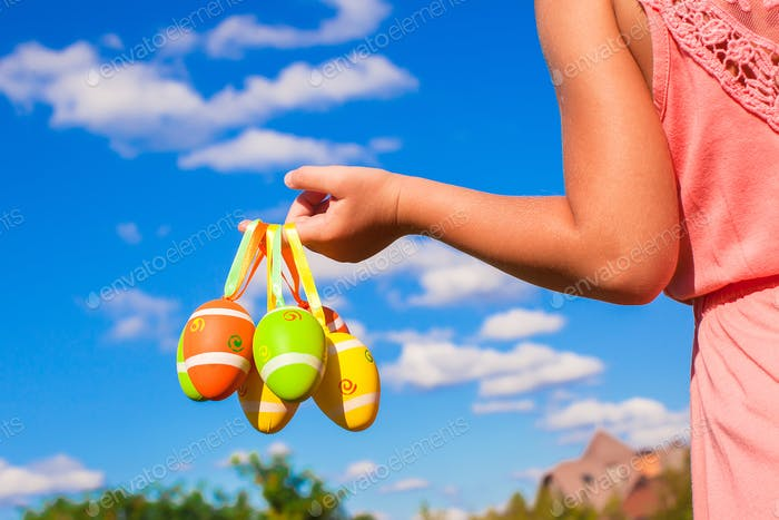 Closeup colorful Easter eggs in the hands of little pretty girl background blue sky
