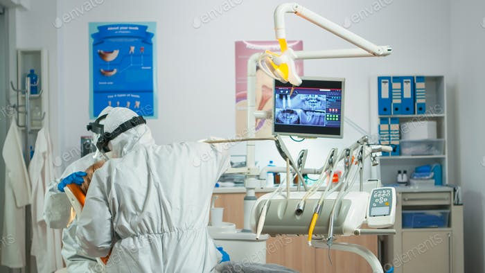 Dentist with face shield working in dental unit during covid-19