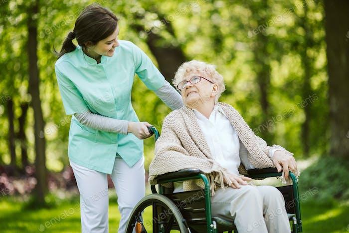 Mujer con discapacidad mayor con cuidador en el jardín de la residencia de ancianos