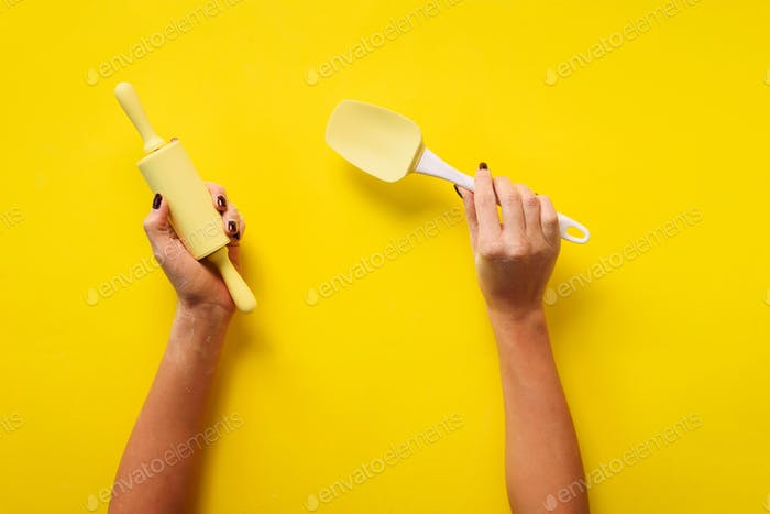 Woman hand holding kitchen utensils on yellow background. Baking tools - rolling pin, spatula