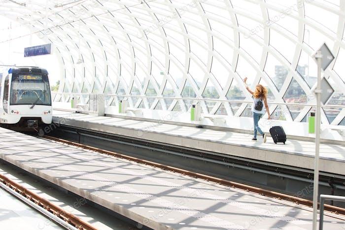 Frau mit Taschen laufen auf Plattform in Bahnhof Zug zu fangen