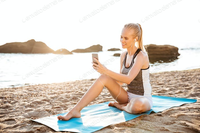Woman doing yoga and using cell phone sitting on mat