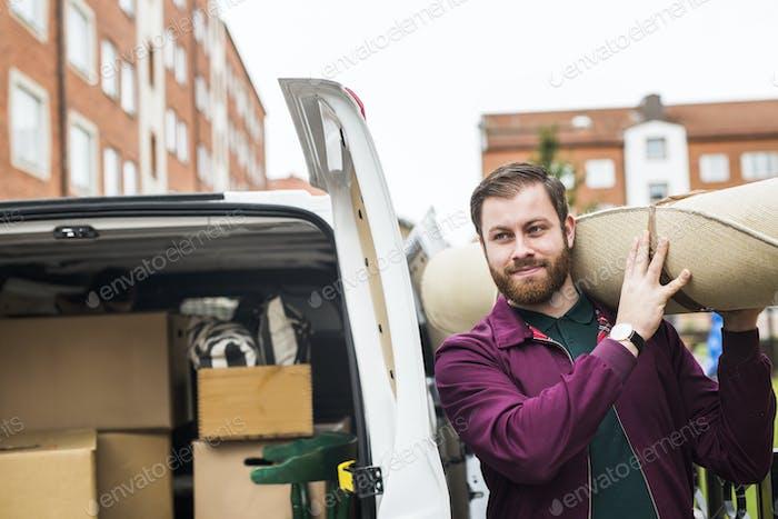 Man loading carpet into rental car